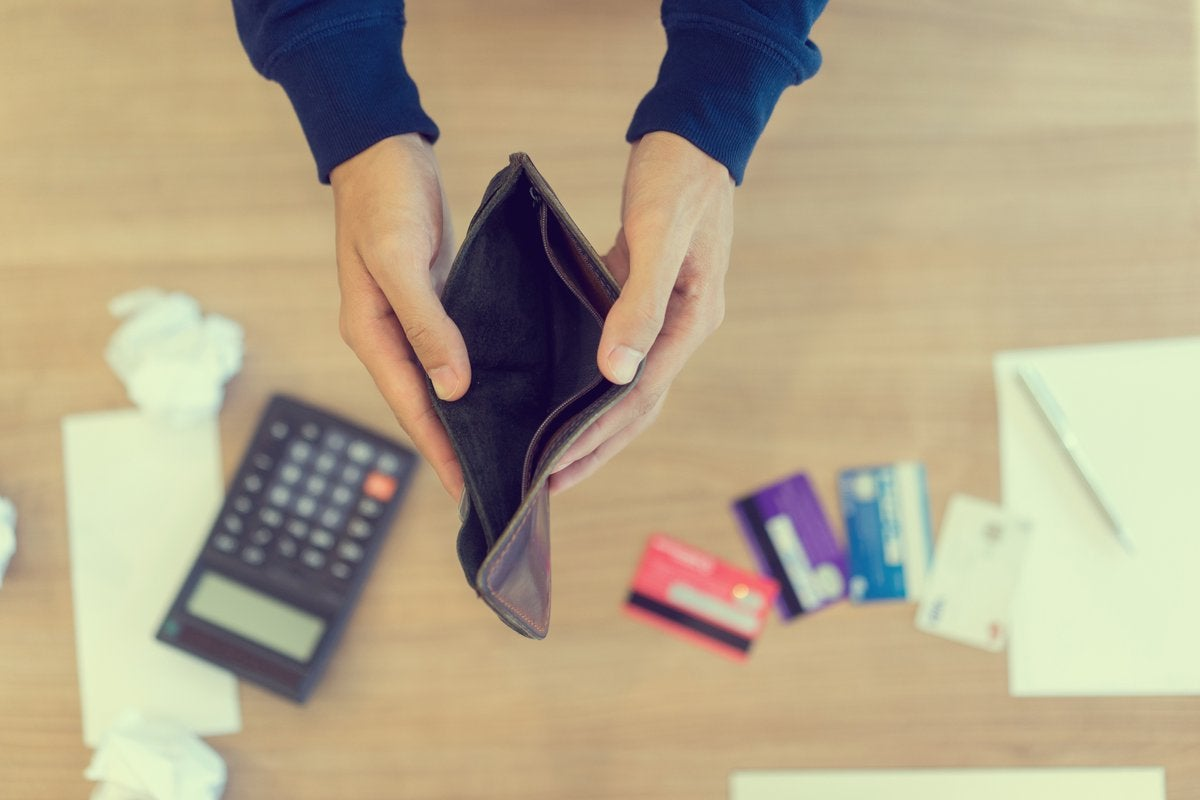 Pair of hands holding an empty wallet open over a calculator and some credit cards on a desk.