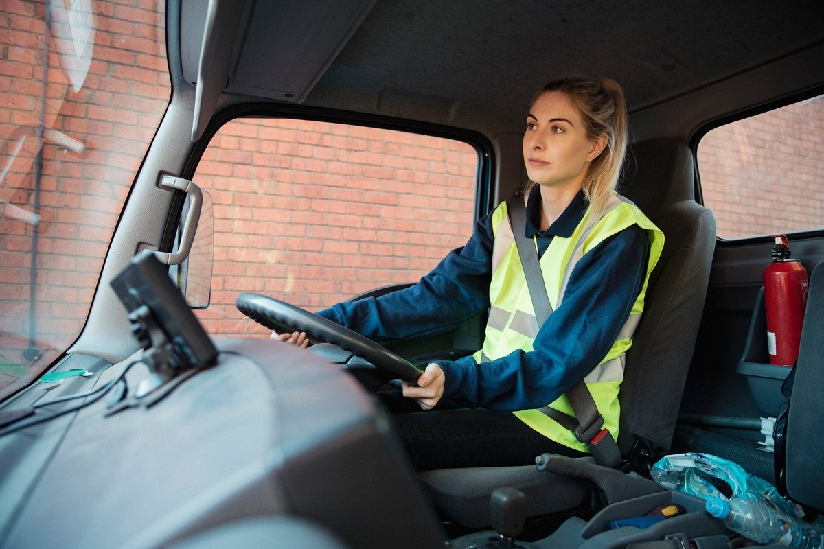 A young adult manual worker drives to work in a van wearing their uniform.