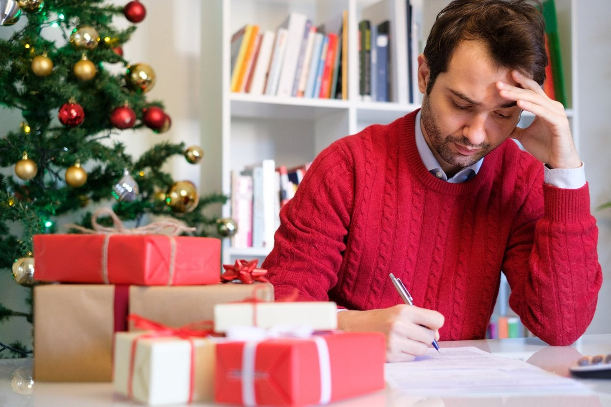 Guy in red sweater stressing over bills while surrounded by Christmas gifts and a Christmas tree.