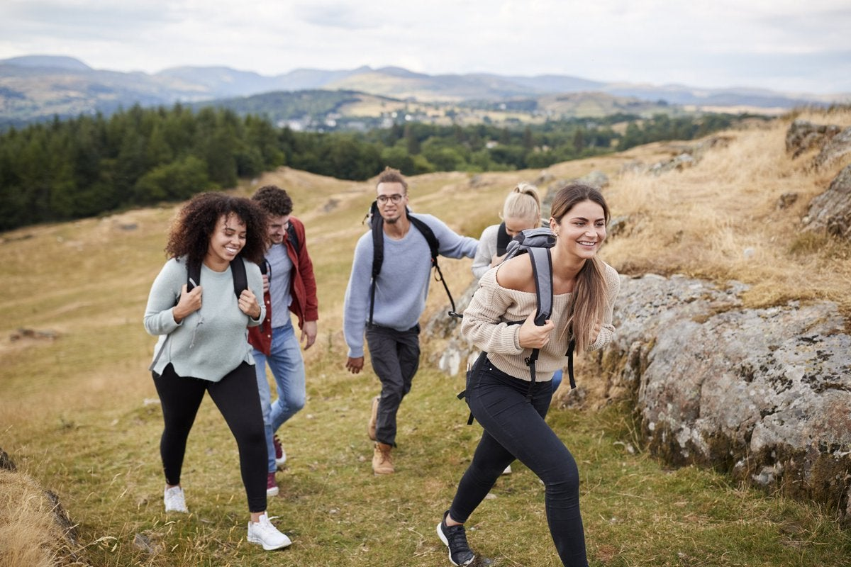 A diverse pack of millennials jubilantly hike up a mountain.