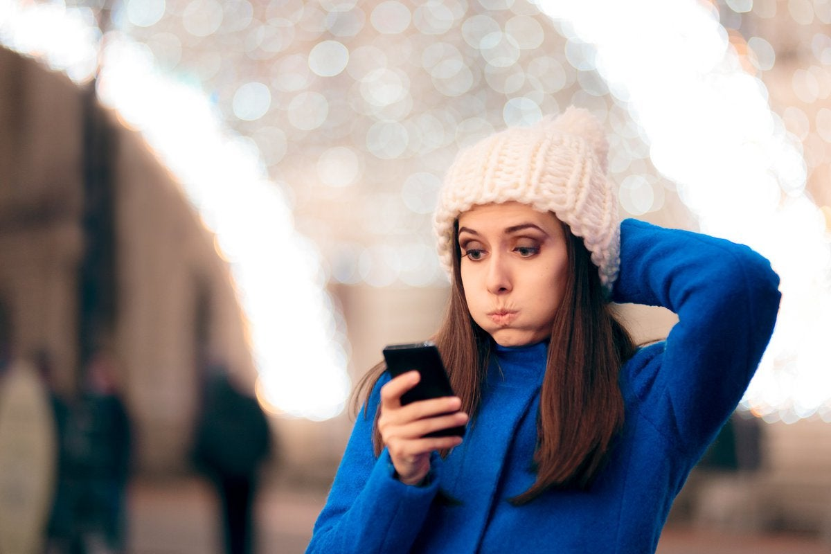 Woman in knit winter hat stressed out while looking at phone.