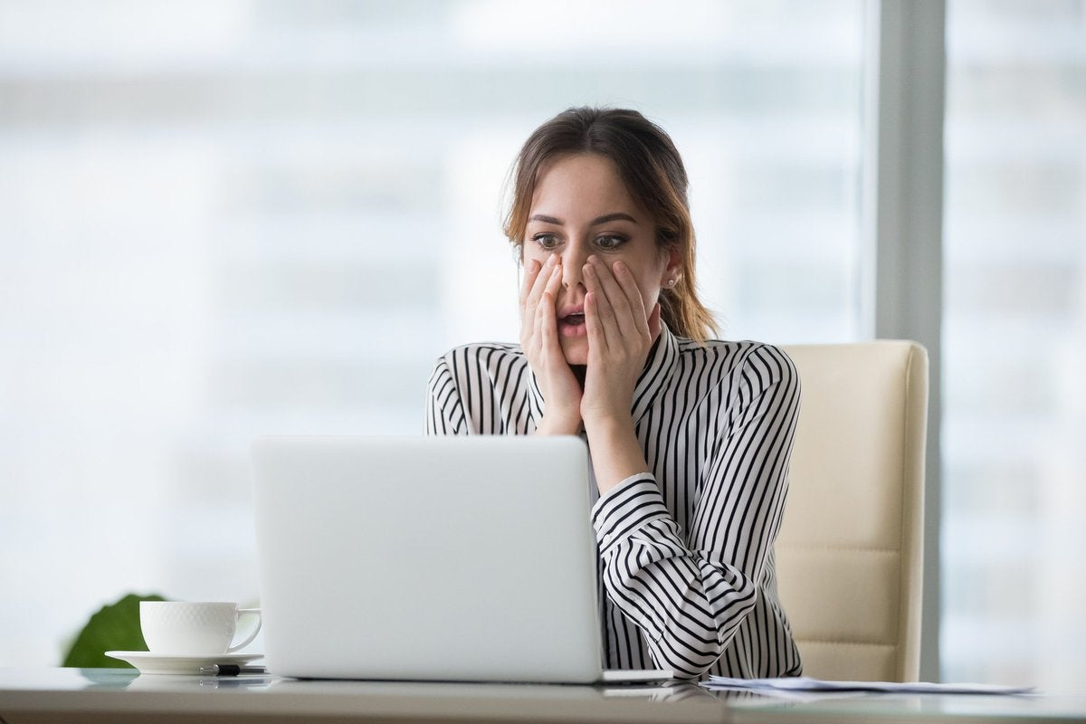 Young woman looking at computer screen from behind desk and pressing her hands to her face as if gasping in horror.
