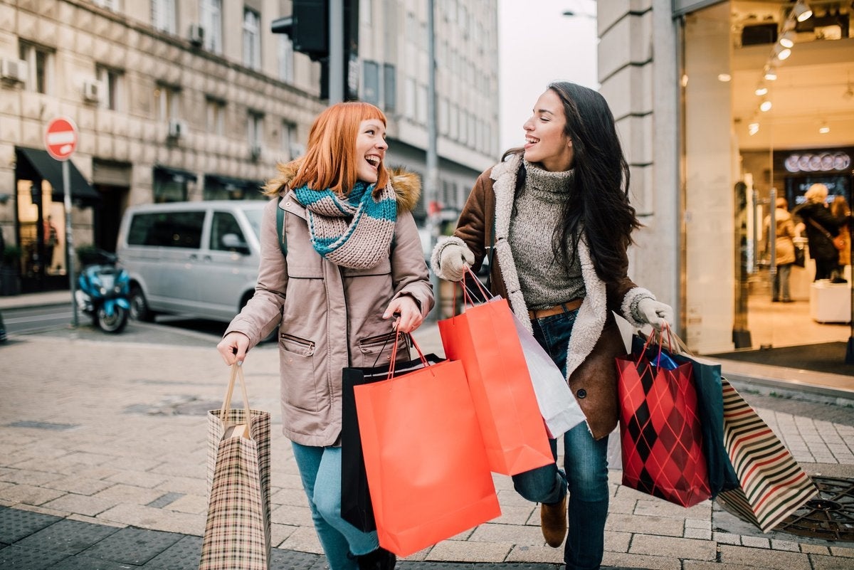 A couple of young women crossing the street and carrying a massive number of shopping bags.