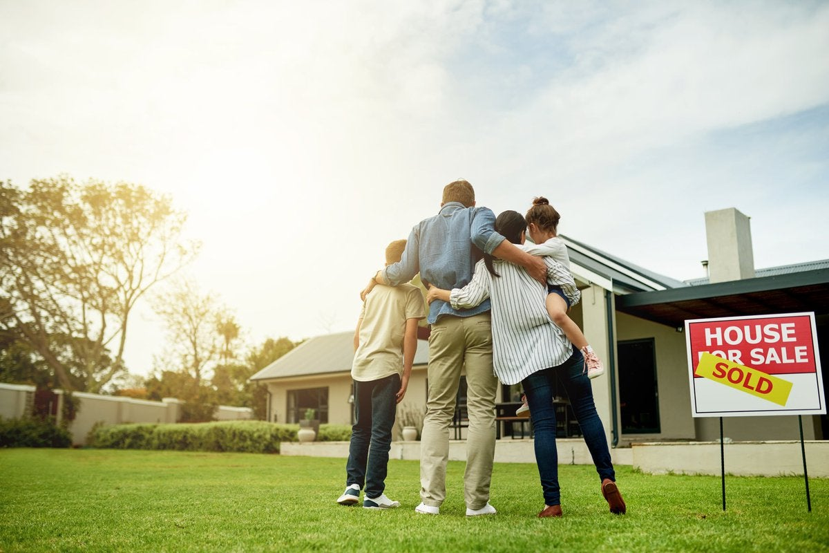 """A family of four, arm in arm, look at a house with a """"Sold"""" sign."""