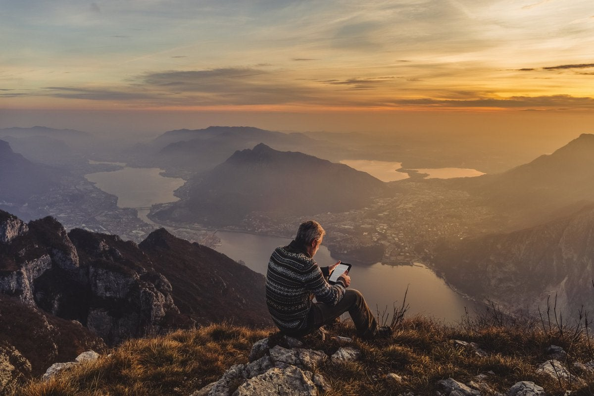 Middle-aged man looking at an iPad while sitting on rocks overlooking a sunset over mountains.