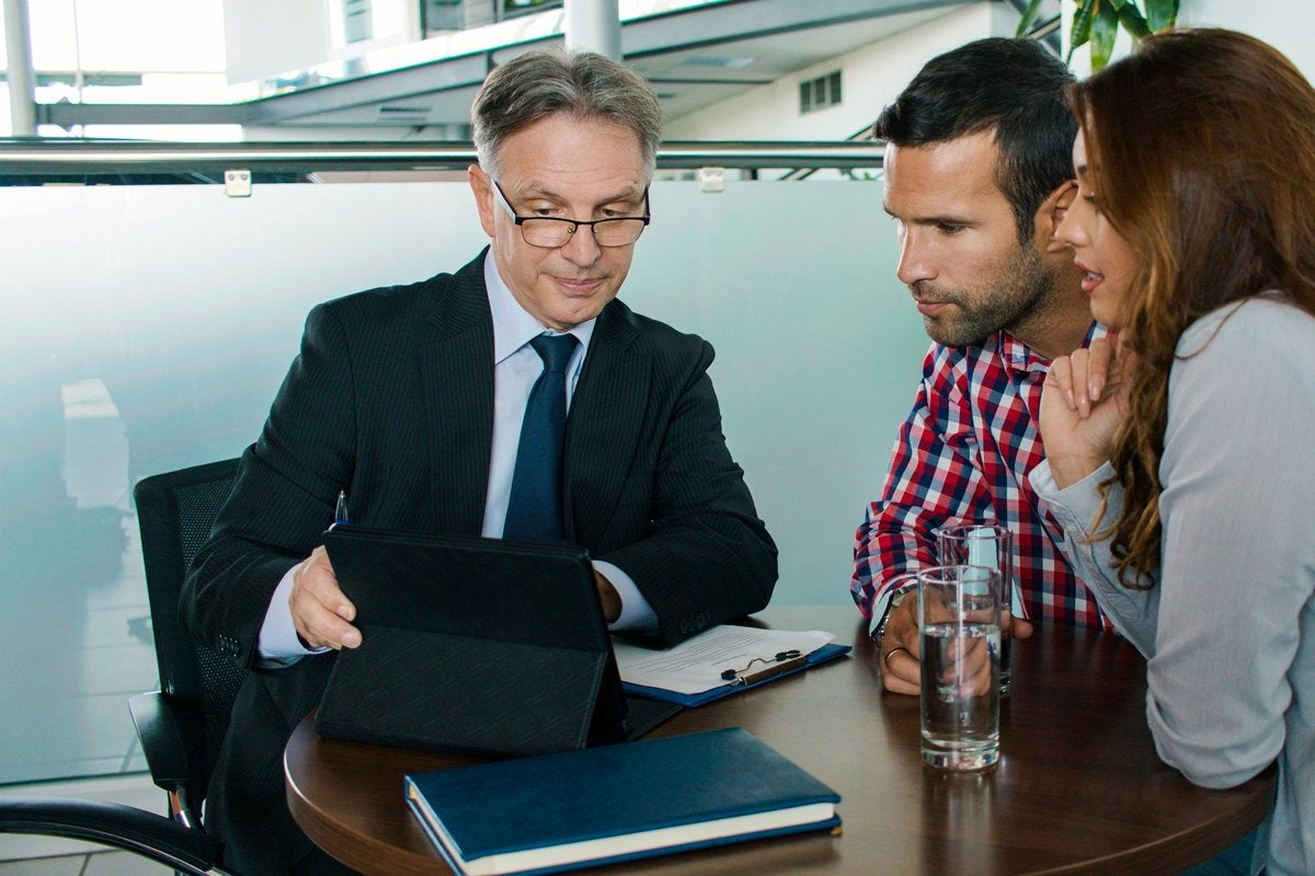 A couple meets with a financial advisor, looking concerned at a tablet screen.