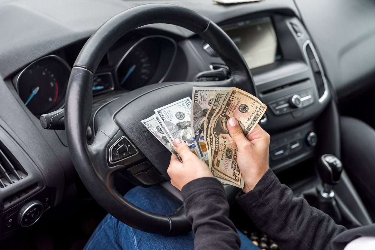 Pair of hands belonging to person sitting in driver's seat of car flipping through a wad of cash.