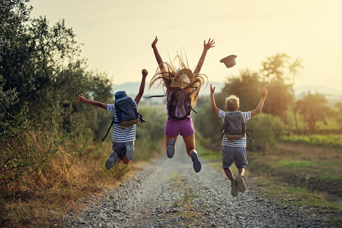 Three children leaping into the air on a gravel path somewhere in nature.