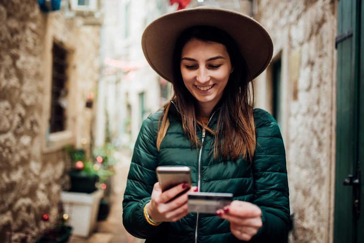 Young woman in hip wide-brimmed hat traveling through an alley in some ancient city grinning down at phone in one hand and credit card in the other.