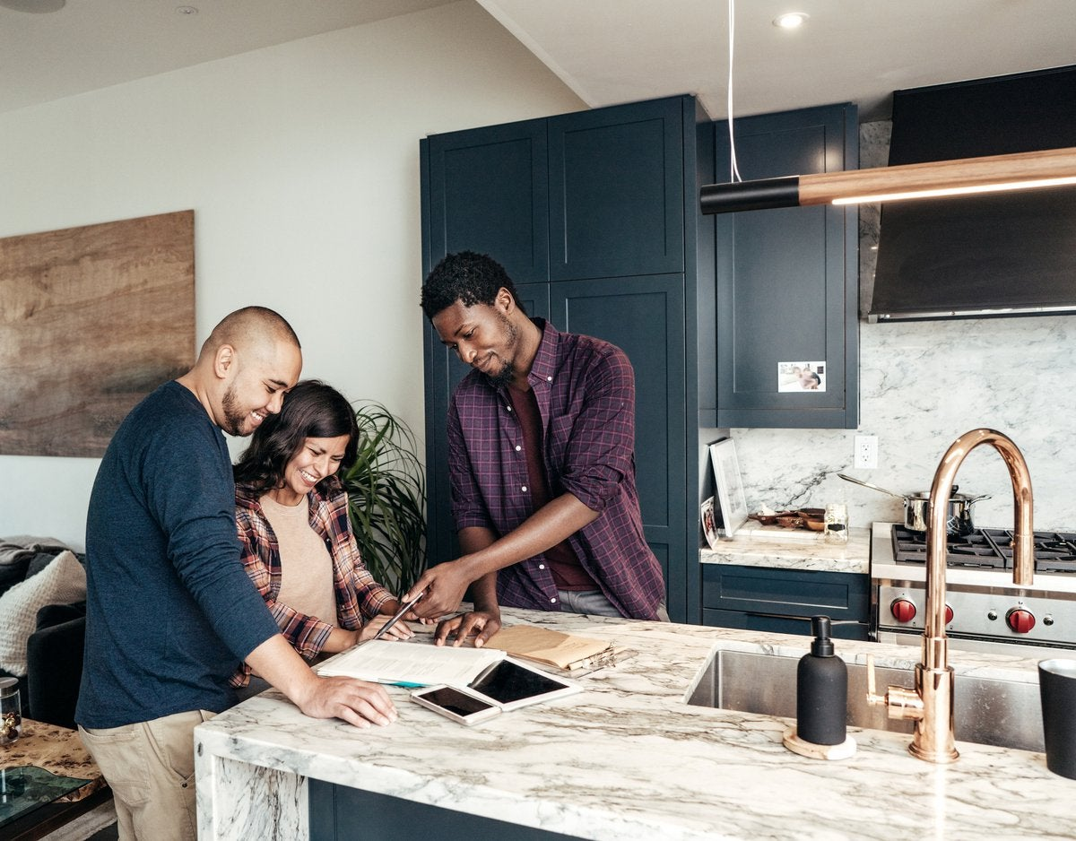 A family meets with a realtor, who points at paperwork and smiles in a kitchen.