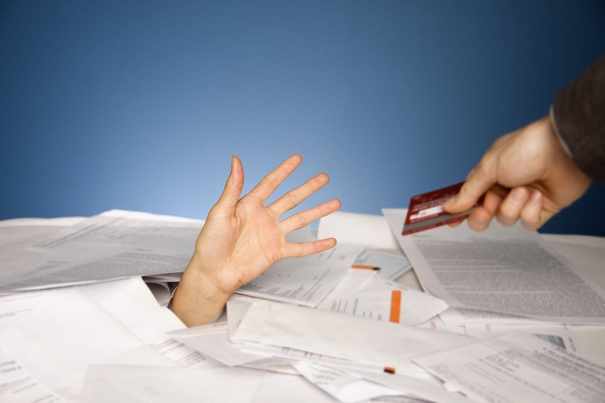 Hand extending credit card to other hand that's reaching out from beneath a pile of bills.