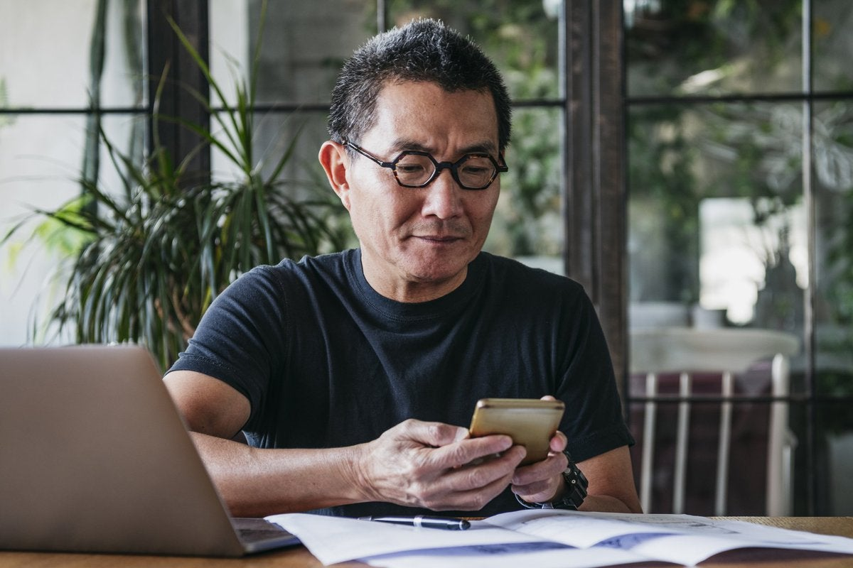 Bespectacled middle-aged man looking at phone while sitting at desk covered in papers.
