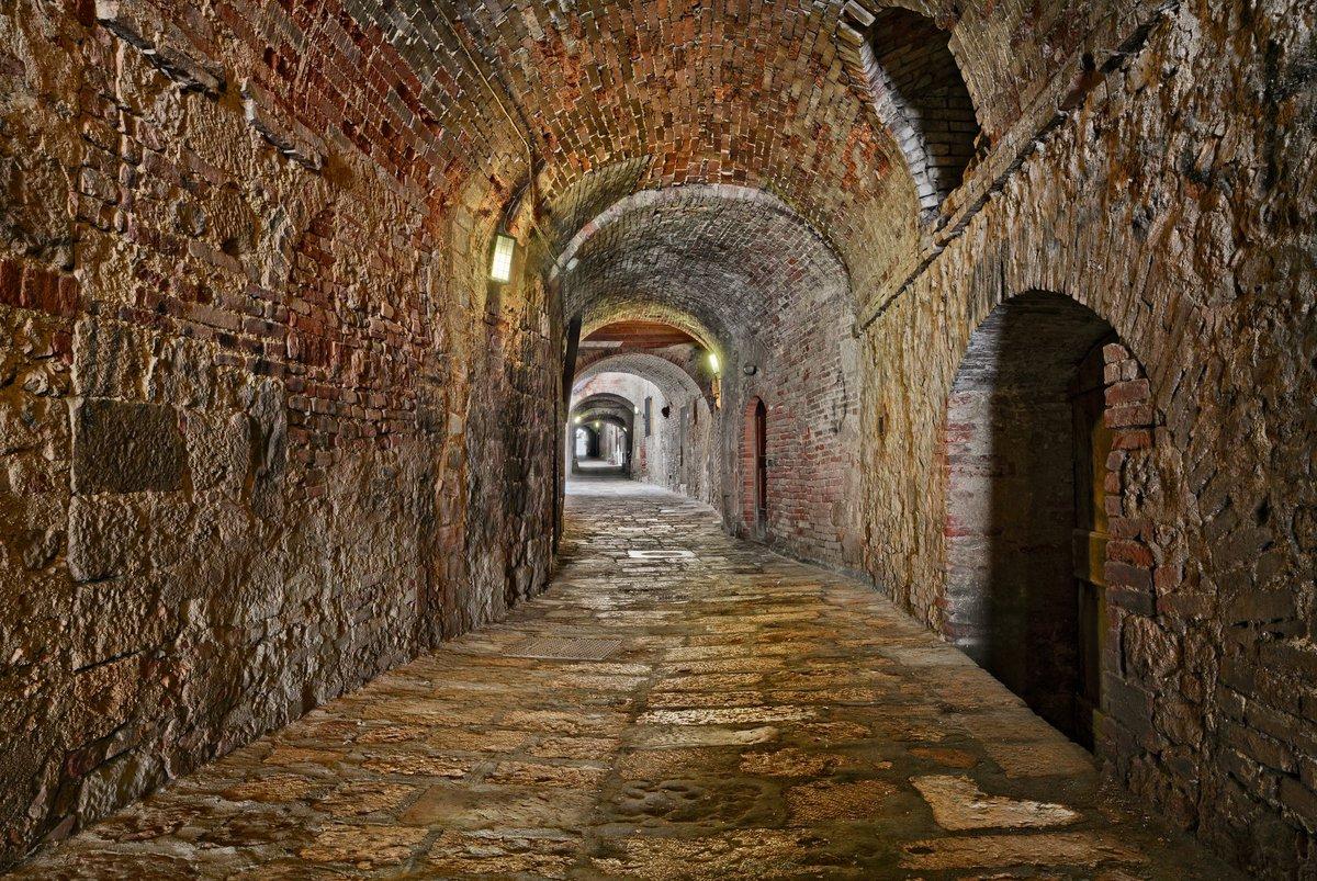 Long hallway through underground catacombs.