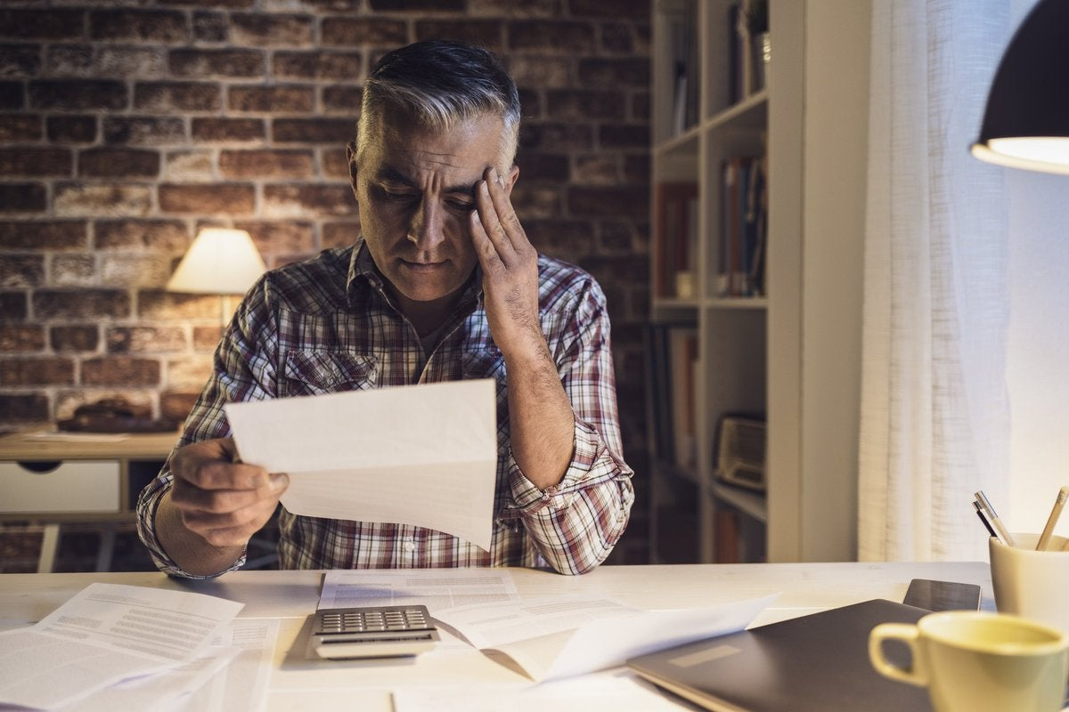Middle-aged man suffering migraine headache caused by bills.