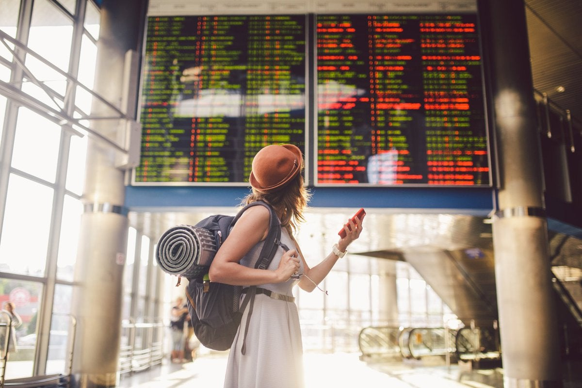 Young woman in airport looking up at flight information board.