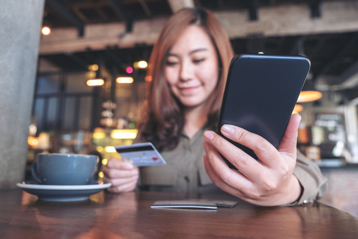 Young woman in coffee shop smiling at her credit card and phone.