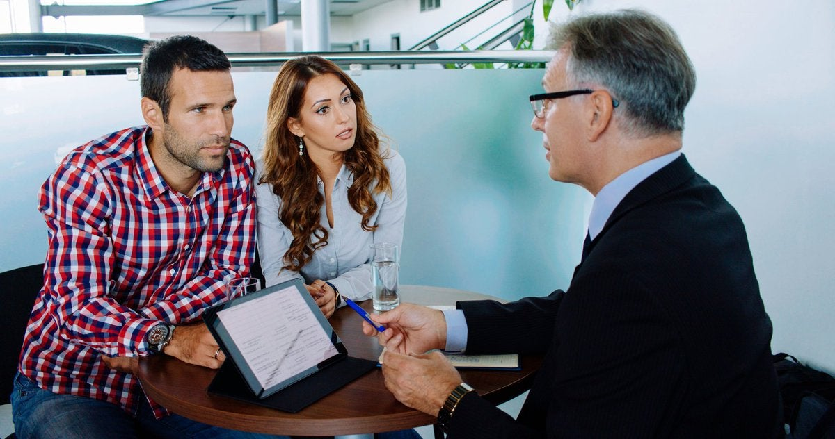A couple discusses their options with a financial advisor in an office.