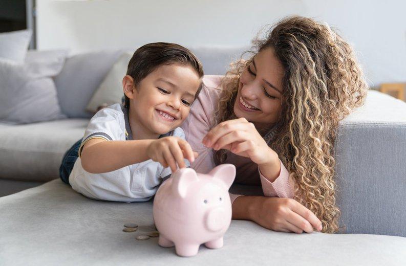 Jovem mãe e criança pequena sorriem enquanto depositam moedas em um cofrinho.