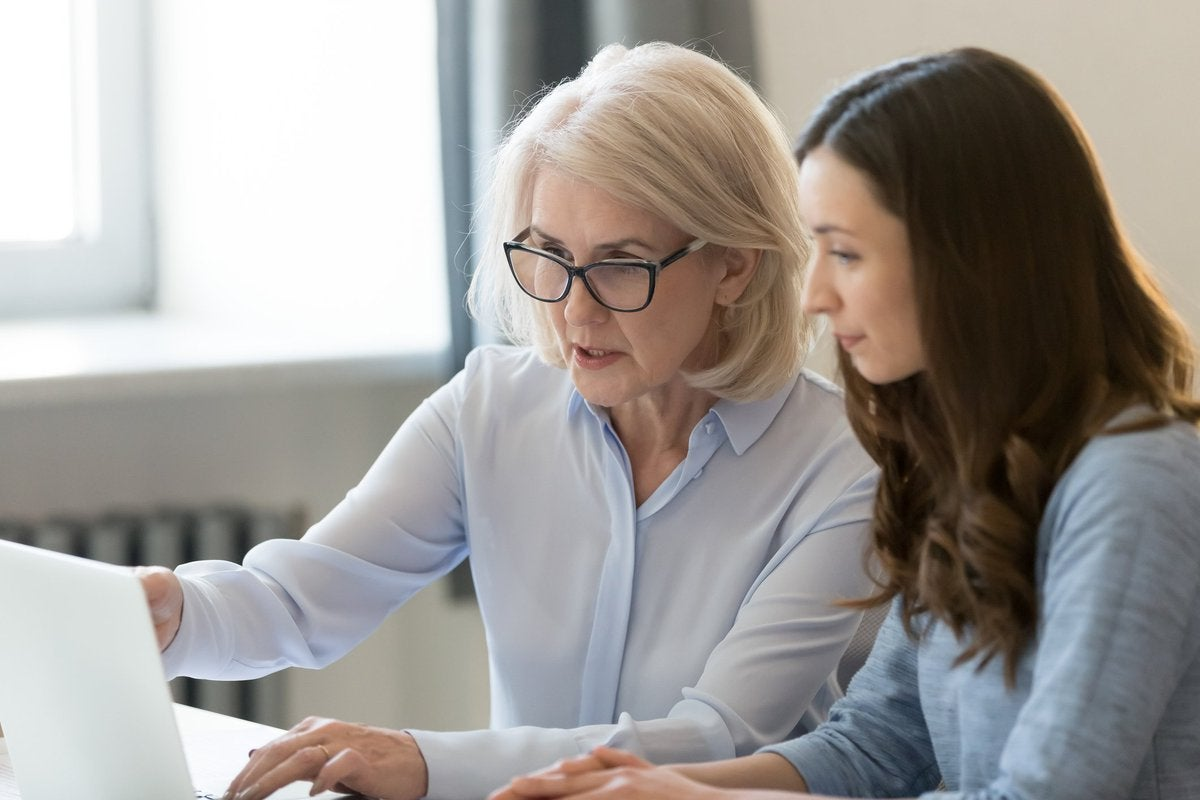 An older woman and a younger woman looking at a laptop screen together.