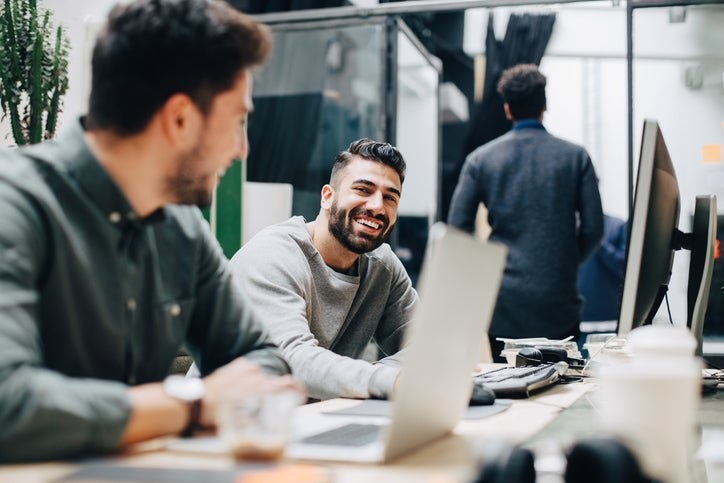 Colleagues with beards laugh together while sitting at desks in an office.