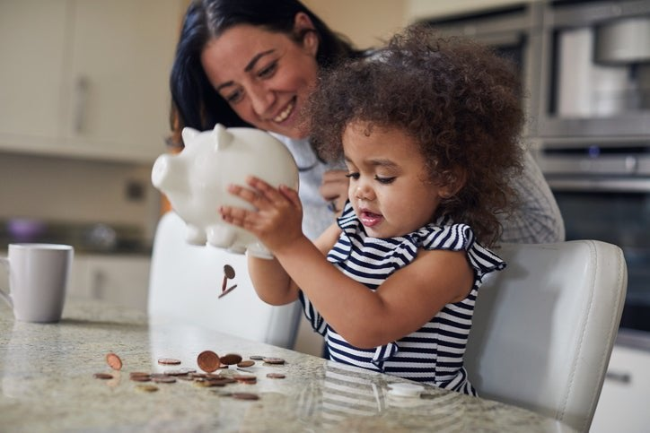 Child shakes money out of a piggy bank as the parent watches and smiles.