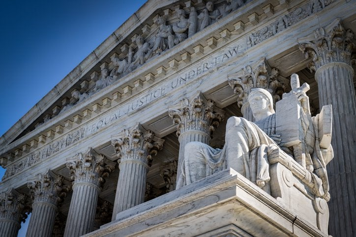 Stone exterior of Supreme Court with Authority of Law statue in foreground.