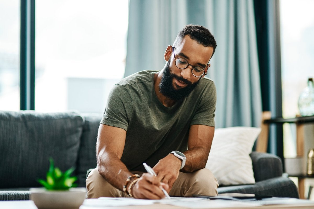 A buff, bearded, bespectacled young man looking relaxed and confident while marking something down on a piece of paper.