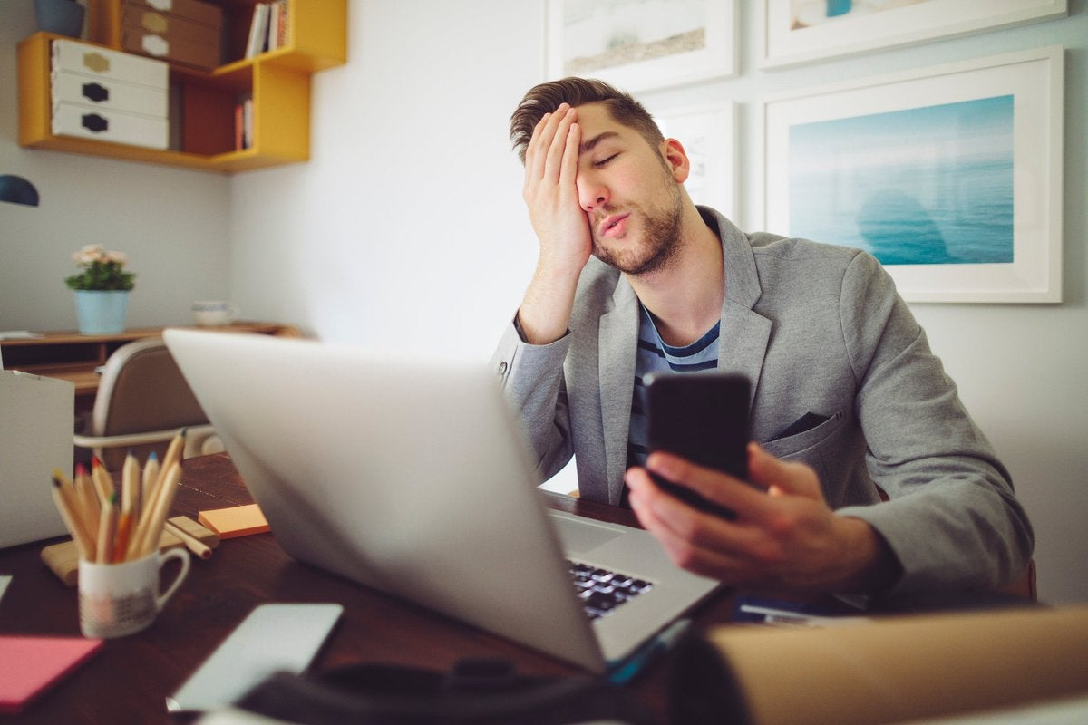Young man puts his hand to his face in frustration while holding his phone and looking at laptop.