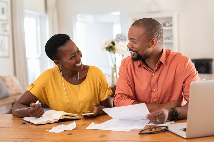 Smiling couple sit at table with paperwork.