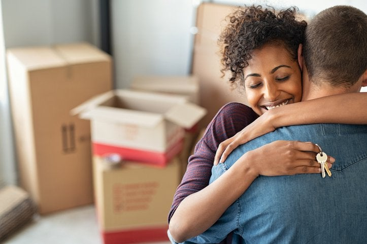 Couple holding keys to new house embrace in foreground, boxes in background.