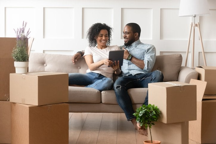 Couple sits on sofa looking at tablet and surrounded by boxes.