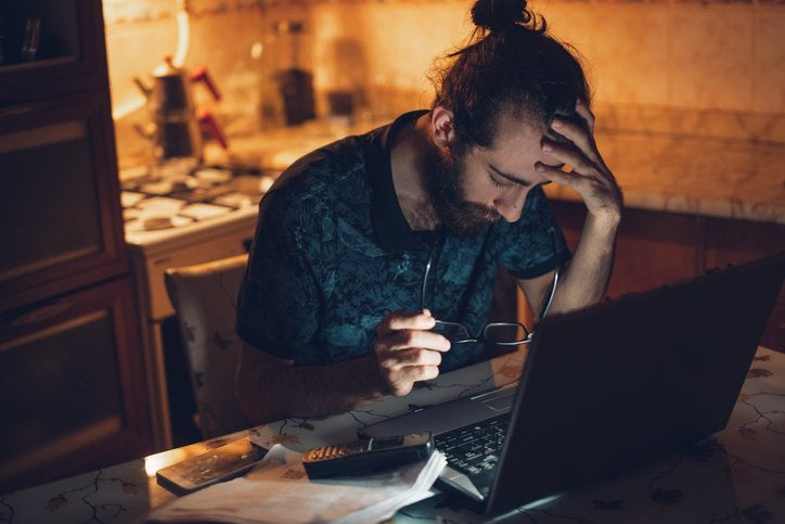 Frustrated man at desk with head in his hands.