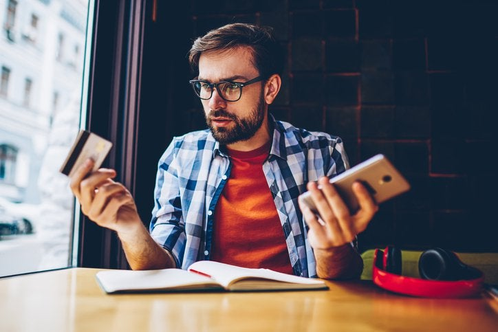 Man in blue checked shirt looks thoughtful with phone in one hand and credit card in the other.