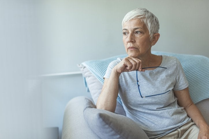 Grey-haired woman holding glasses rests hand on chin and looks thoughtful.