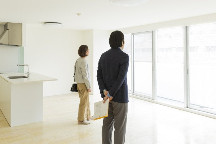 Two prospective buyers look out of window in new apartment.