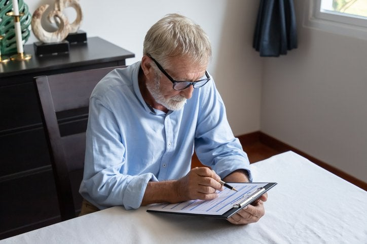 Grey-haired man sits at table and fills in form on clipboard.