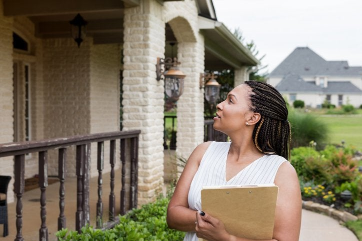 Woman stands outside house with a clipboard
