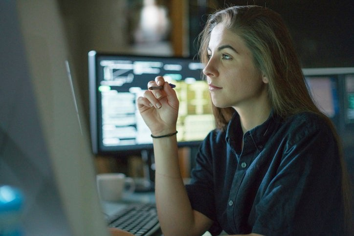 A young woman sits at a desk surrounded by monitors displaying financial data.