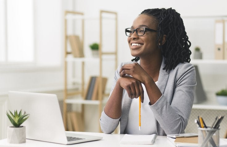 Happy woman at computer with pencil in her hand.