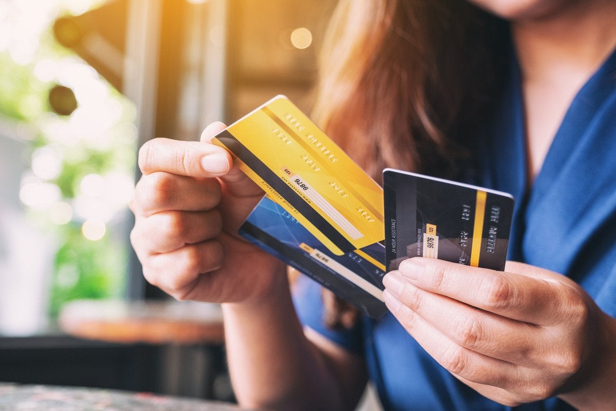 Woman choosing and removing one credit card from a set of three.
