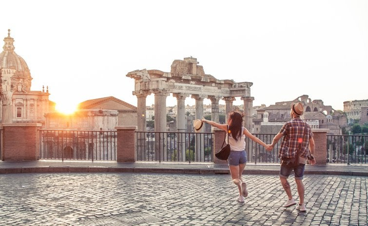 Young couple walk towards the Roman Forum in Rome as sun sets.