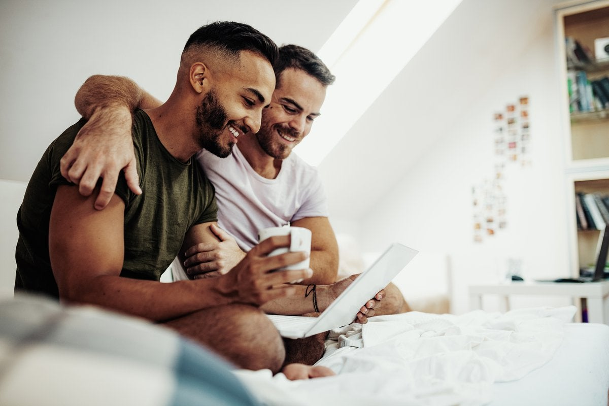 A couple sits in bed drinking coffee and smiling at something on a laptop screen.