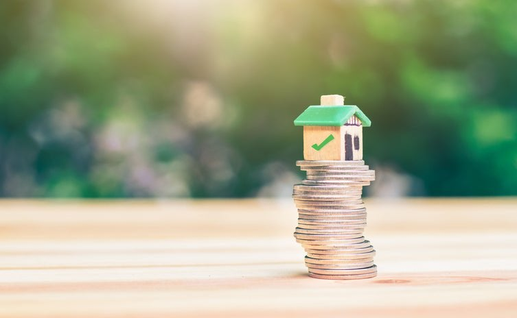Small wooden house sits atop a stack of coins