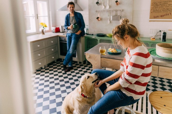 Woman with dog in kitchen foreground, while man looks on.