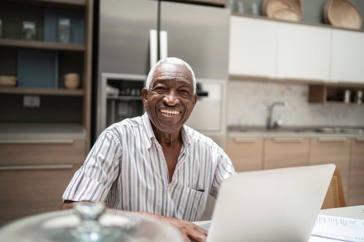 Man with broad smile on his face sits in front of computer.