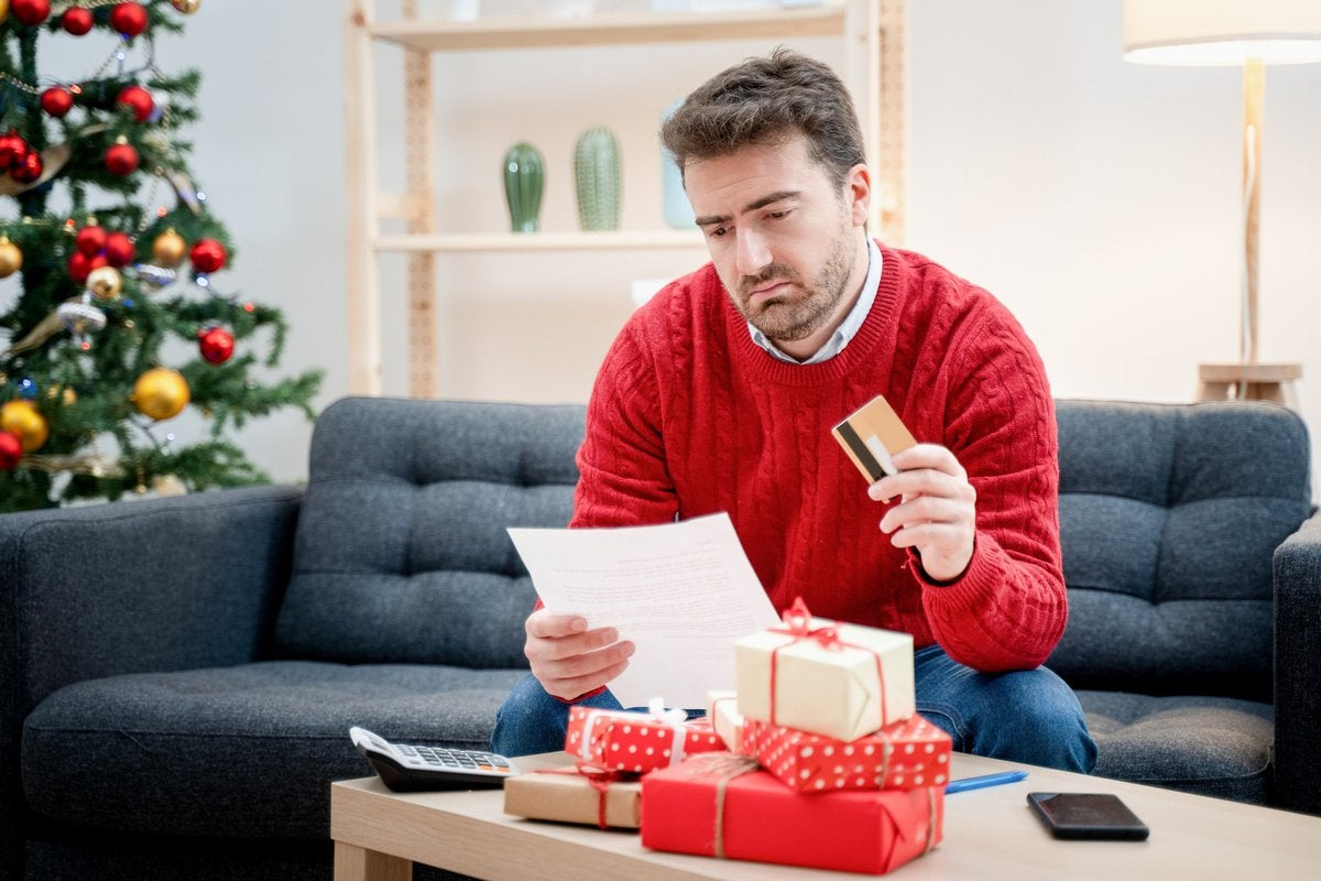 Man in Christmas sweater sitting in front of a pile of gifts while holding a credit card and looking at a document.