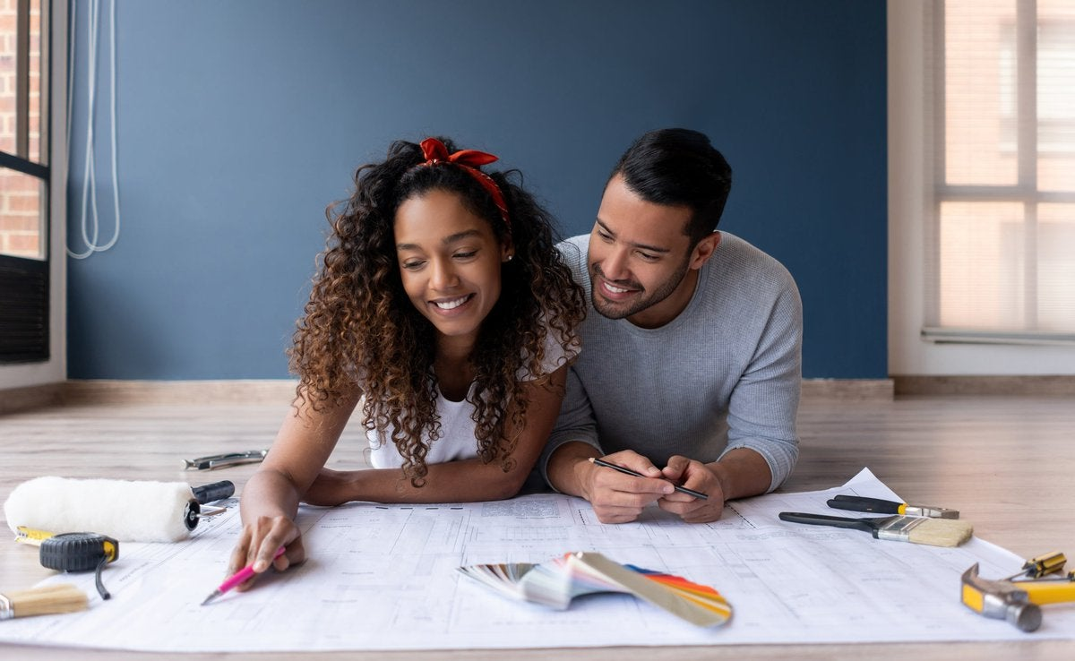 A couple looks at the blueprints of their new house while lying on the floor smiling.