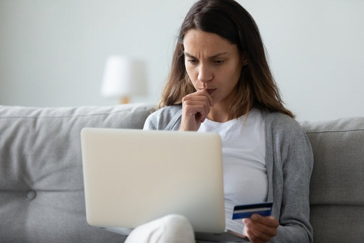 Woman on sofa with credit card in her hand and laptop.