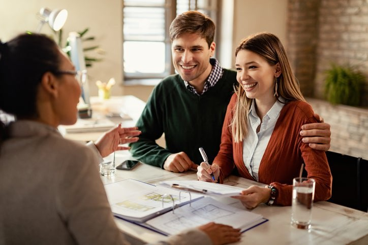Happy couple in conversation with a business professional at a desk