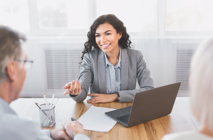 Smiling woman gestures to gray-haired man over desk.